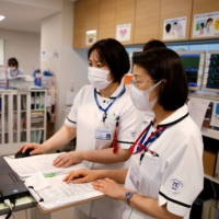 Satsuki Nakayama (right), director of the nursing department at Osaka Medical and Pharmaceutical University Hospital, works with her colleague in the operation wing of the hospital in Takatsuki, Osaka Prefecture, on May 17.   REUTERS