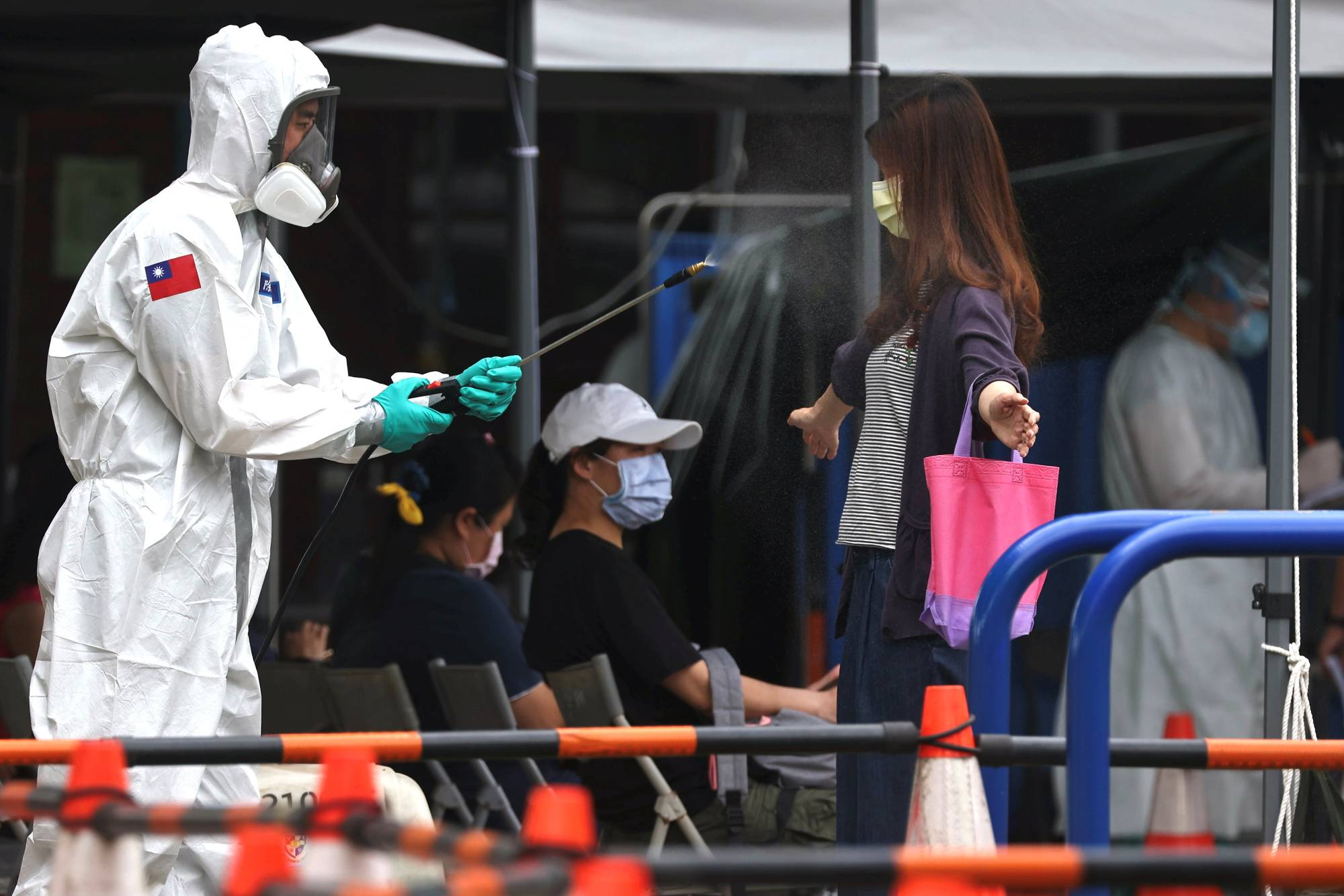 A soldier disinfects a person departing a COVID-19 testing site in Taipei on Wednesday.    REUTERS