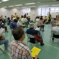 People wait to be processed after arriving to receive the Moderna COVID-19 vaccine at a newly opened mass vaccination center in Tokyo on Monday.   POOL / VIA REUTERS
