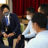 Masato Matsuo (left), director at the Kyushu branch of Second Chance!, interacts with young offenders at the Fukuoka Juvenile Reformatory in March 2021. (Faces have been pixelated for privacy reasons.) | KYODO