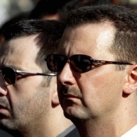Syrian President Bashar Assad and his brother, Maher, attend their father's funeral in the capital, Damascus, in June 2003. | AFP-JIJI