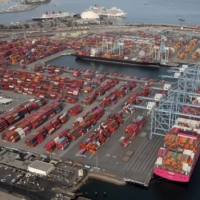 Shipping containers are unloaded at the Port of Long Beach-Port of Los Angeles complex in April.  | REUTERS