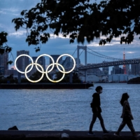 The Olympic rings are lit at dusk on the Odaiba waterfront in Tokyo on April 28. | AFP-JIJI