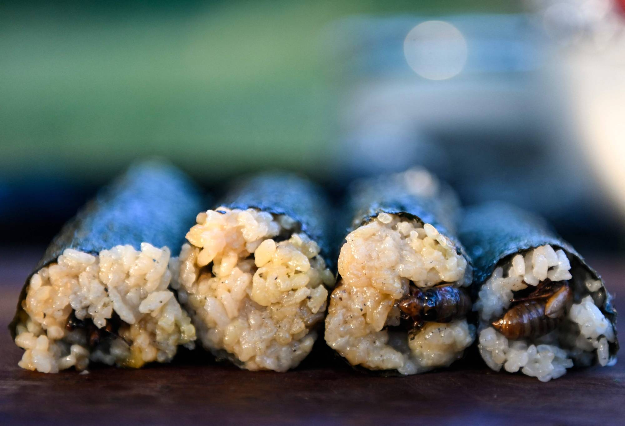 Fried cicadas are rolled into a sushi roll by chef Bun Lai at Fort Totten Park in Washington on Sunday.   AFP-JIJI