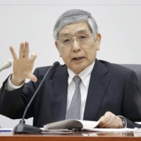 Bank of Japan Gov. Haruhiko Kuroda says he is starting to see the light at the end of the dark pandemic tunnel thanks to the rollout of COVID-19 vaccines. | POOL / VIA KYODO