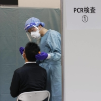 A quarantine official conducts a COVID-19 test on a passenger after their arrival at Narita Airport. | KYODO