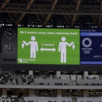 COVID-19 precautions are displayed on a big screen prior to an athletics test event for the Tokyo 2020 Olympic Games, at the National Stadium in Tokyo on May 9. | BLOOMBERG