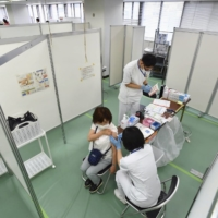 A senior citizen is inoculated against COVID-19 at a large-scale vaccination center in Osaka Prefecture on Monday.   KYODO