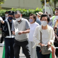 Staff members guide people at a large-scale coronavirus vaccination center in Tokyo. The capital reported 542 new cases of COVID-19 on Tuesday.   REUTERS