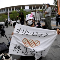 Anti-Olympics protester shows off a banner with the National Stadium in the background outside the Japanese Olympic Committee's headquarters during a rally in Tokyo last week. | REUTERS
