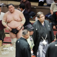 Terunofuji watches as ringside officials discuss his victory against Myogiryu on May 19 at Ryogoku Kokugikan. The ozeki was handed a loss after he was judged to have grabbed his opponent's hair during the bout. | KYODO