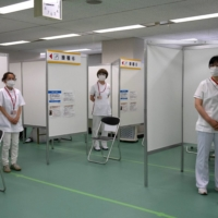 Nurses wait to inoculate people with a dose of the Moderna Inc. COVID-19 vaccine in Tokyo on Monday. Among the public, the government's handling of the pandemic and vaccine rollout is eroding feelings of patriotism.   BLOOMBERG