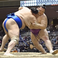 Asanoyama (right) withdrew from the Summer Basho after he was found to have violated the Japan Sumo Association's coronavirus safety protocols. | KYODO