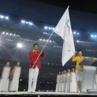 Chinese table-tennis player Zhang Yining (right) takes the Olympic Oath during the opening ceremony of the 2018 Summer Games on Aug. 8, 2008, in Beijing. | REUTERS