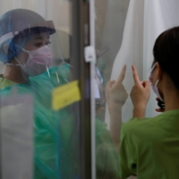 COVID-19 infections are declining in some areas including Tokyo and Osaka but 'on the whole the situation is highly unpredictable,' Prime Minister Yoshihide Suga said. | REUTERS