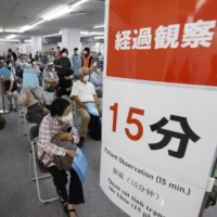 People wait after receiving coronavirus vaccine shots at a newly opened vaccination center in Kobe on May 25.  | KYODO