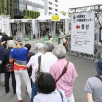 People line up in front of a mass-inoculation center in Tokyo's Chiyoda Ward on Wednesday to be vaccinated against COVID-19.   KYODO