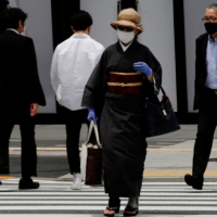 A woman walks through a shopping district in Tokyo on Friday.   REUTERS