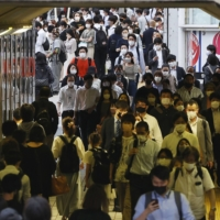People walk in the Shinjuku district of Tokyo on Wednesday. | KYODO