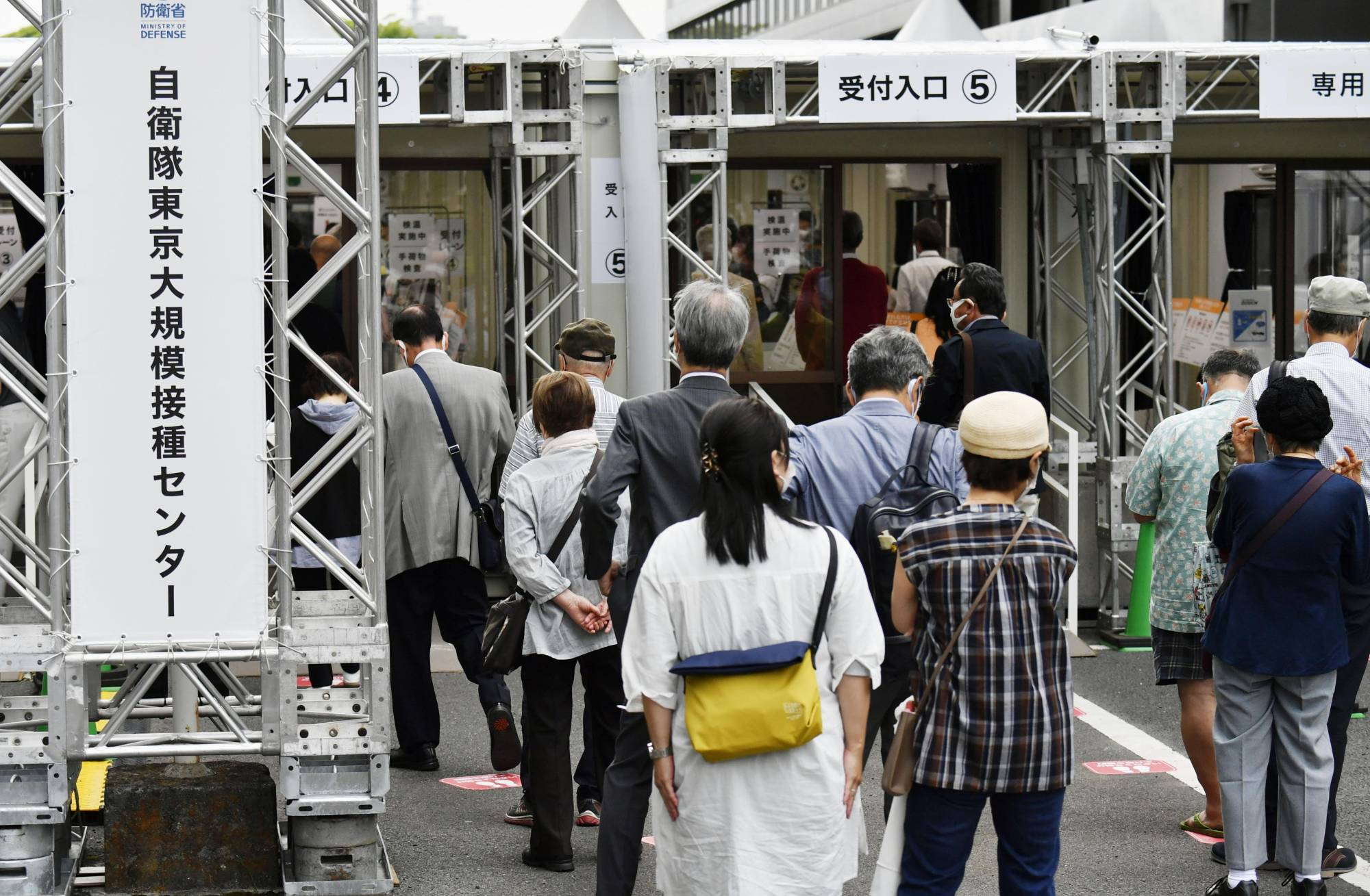 People line up in front of a mass inoculation center in Tokyo's Chiyoda Ward to receive a COVID-19 vaccine on Wednesday.   KYODO