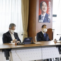Tsutomu Sato (left) and other lawmakers attend a meeting of the Liberal Democratic Party's General Council at the party's headquarters in Tokyo on Friday.