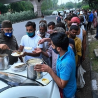 Homeless people line up for food distributed by volunteers in New Delhi earlier this month.  | AFP-JIJI