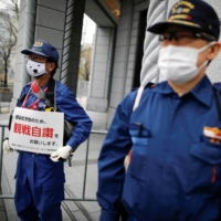 A firefighter holds a sign that reads 'In order to prevent infection, please refrain from watching,' along the route before the start of the Hokkaido-Sapporo Marathon Festival 2021, a half-marathon and a 10K race which is a test event for the Tokyo 2020 Olympics marathon race, amid the coronavirus outbreak, in Sapporo, Hokkaido on May 5.  | REUTERS