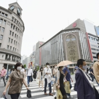 Pedestrians cross a street in Tokyo's Ginza area on Saturday, as a COVID-19 state of emergency remains in place in the capital. | KYODO