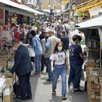People stroll outside the Tsukiji Outer Market in Tokyo on Saturday.  | KYODO