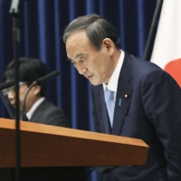 Prime Minister Yoshihide Suga bows during a news conference on Friday in announcing an extension of the current state of emergency for Tokyo and other prefectures. | POOL / VIA KYODO