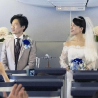 A pilot holds up a certificate of marriage for Toru Murakami (center) and Mami Murakami (right) at an onboard wedding held in an All Nippon Airways Co. Boeing B-777 at Tokyo's Haneda Airport on May 23. | ANA / VIA KYODO
