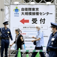 People are guided to the mass vaccination center run by the Self-Defense Forces in Tokyo.    KYODO
