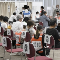 Older people are vaccinated against COVID-19 at the state-run mass vaccination center in Osaka.   KYODO