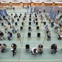 Older people wait to receive a dose of a COVID-19 vaccine at Fujita Health University gymnasium, a newly opened large-scale coronavirus disease vaccination center in Toyoake, Aichi Prefecture, on May 24.   KYODO