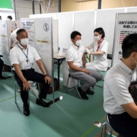 A health worker administers the Moderna COVID-19 vaccine during the first round of vaccinations for firefighters in Tokyo on Tuesday. | AFP-JIJI