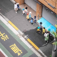 Children are accompanied by guardians as they walk to a kindergarten in Tokyo amid the coronavirus pandemic. | AFP-JIJI
