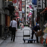 Pedestrians walk through an alley of restaurants and bars in Tokyo on May 18. G7 governments have been pumping trillions of dollars into their economies to keep them alive since the start of the pandemic in March 2020. | AFP-JIJI