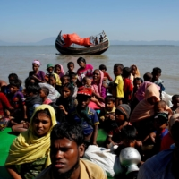 Rohingya refugees sit on a makeshift boat as they are interrogated after crossing the Bangladesh-Myanmar border at Shah Porir Dwip, near Cox's Bazar, Bangladesh, in November 2017. | REUTERS