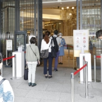 Shoppers enter Mitsukoshi department store in Tokyo's Ginza district as it fully reopened on Tuesday.   KYODO