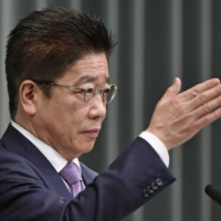 Chief Cabinet Secretary Katsunobu Kato speaks at a news conference Tuesday to announce the start date of COVID-19 inoculation program at workplaces and universities.   KYODO