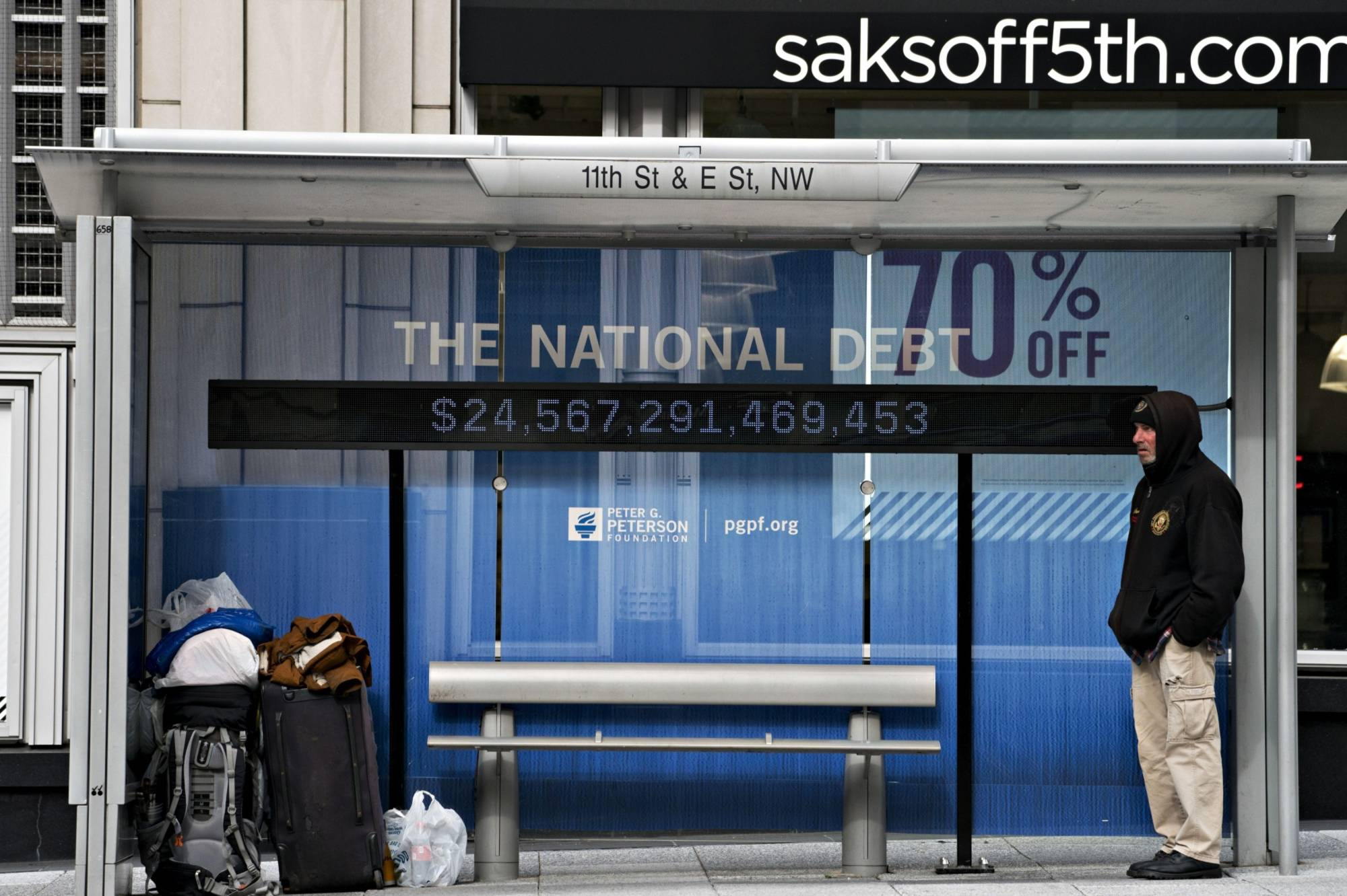 A national debt counter hangs inside a bus stop in Washington on April 23, 2020. | BLOOMBERG