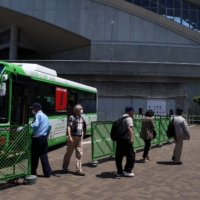 People arrive via a bus to receive a dose of the Pfizer-BioNTech COVID-19 vaccine at a mass-inoculation site at Noevir Stadium Kobe on Tuesday. After some false starts, Japan's much-delayed vaccine rollout is quietly picking up steam, now administering between 400,000 and 500,000 doses a day.    BLOOMBERG