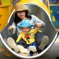 A mother and her baby play on a slide in Beijing. China has relaxed its family planning policy to allow couples to have three children.  | AFP-JIJI