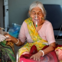 And 80-year-old woman infected with the COVID-19 virus arrives at a hospital for treatment in Ahmedabad, India, on May 5. | REUTERS
