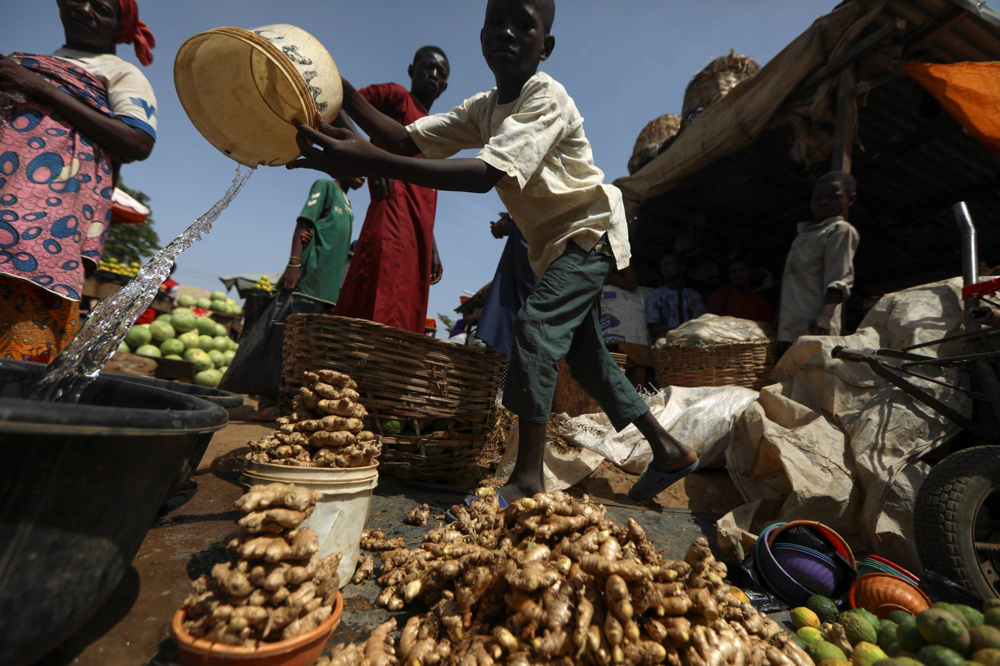 A boy pours water into a container to wash fresh ginger at a market in Kaduna, Nigeria. | REUTERS