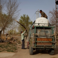 Wang Tianchang, 78, a veteran of China's state campaign to 'open up the wildernesls,' helps his son, Wang Yinji, fill a water tank before driving into the desert to plant trees, at his house on the outskirts of Wuwei.  | REUTERS