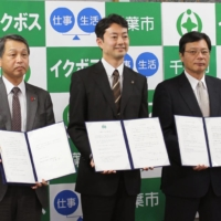 Chiba's then-Mayor Toshihito Kumagai (center) makes a declaration in November 2015 at Chiba City Hall with others among government, industry and academia to foster management that will promote paternity leave. | KYODO