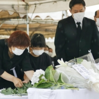 Sumi Omachi (left), who lost her husband in the 1991 eruptions of Mount Unzen's Fugen Peak, lays flowers at a memorial service in Shimabara, Nagasaki Prefecture, on Thursday.   KYODO