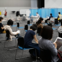 Around 200 nurses — most of whom volunteered to help at a vaccination site set to open on June 8 at the former location of Tsukiji Market — received their first dose Sunday at the Tokyo Nursing Association office in Shinjuku Ward. | RYUSEI TAKAHASHI