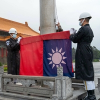 Honor guards raise a Taiwanese flag at the National Chiang Kai-shek Memorial Hall in Taipei on Wednesday. | BLOOMBERG